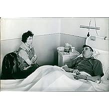 Vintage Photo de la mujer ver Su Marido como él dormir en una cama de hospital.