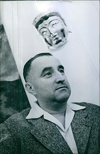 vintage-photo-of-a-photo-of-a-man-looking-for-something-and-a-maskara-behind-him-1964