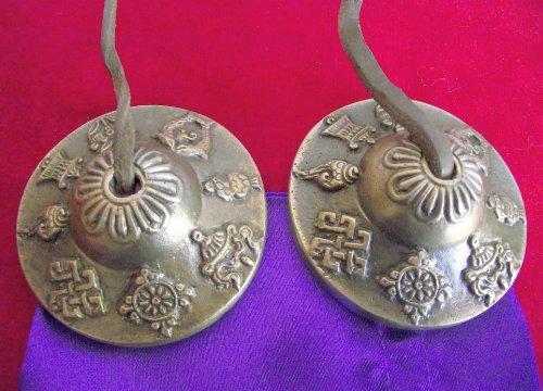 Tibetanos budistas Astamangala Campanas de la mano en la cuerda de cuero; relieve con los 8 símbolos budistas de la Felicidad - Diámetro 60 mm; viene en una bolsa con cordón de raso. Uso como ayuda para la meditación; para despejar el espacio, la curación - Vendido por dones espirituales. Por lo general, enviamos dentro de 2 días laborables.