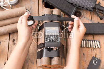 Wunschmotiv: Hands handling homemade bomb with explosives and cellular phone attached wires sitting on surface next to other used parts, machine gun in background #119719451 - Bild als Klebe-Folie - 3:2 - 60 x 40 cm / 40 x 60 cm -
