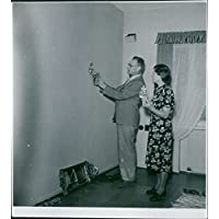 Vintage photo of Finnish-Russian War 1939-40A couple trying to fit some wall ornament after they evacuated in a new home during the war. 1940