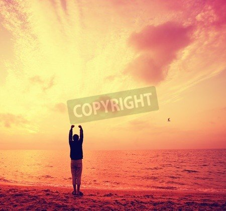 """Poster-Bild 90 x 80 cm: """"Silhouette of young man with hands in the air on the beach at sunrise"""", Bild auf Poster"""