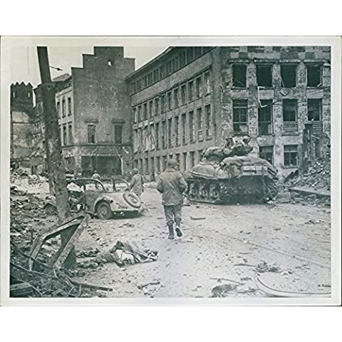 Army troop proceeding through the street of war battered cologne.