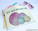 Porta lanas para tejedoras, bolso de polipiel de color claro con rayas en amarillo pastel, lleva asa lateral de ganchillo en amarillo y un abalorio en oro antiguo en forma de ovillo.