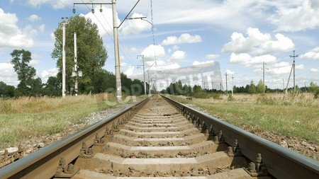 """Poster-Bild 70 x 40 cm: """"Railroad track in countryside in perspective on blue sky background. View from ground of train tracks and flying butterflies in """", Bild auf Poster"""