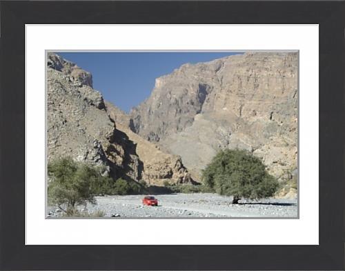 framed-print-of-gravel-road-along-the-floor-of-deep-wadi-below-limestone-cliffs-wadi-bani-habib