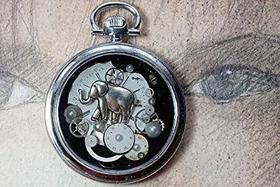 """Pendentif unisexe steampunk""""mémoire d'éléphant"""" fait d'un boitier de montre vintage recyclé couleur argent avec un cadran, des rouages, un petit élephant des cabochons nacrés, de la résine cristal."""