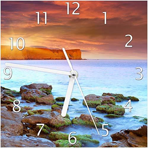 Wallario Glas-Uhr Echtglas Wanduhr Motivuhr; in Premium-Qualität; Größe: 20x20cm; Motiv: Sonnenaufgang am Meer mit Landzunge und Felsen im Wasser