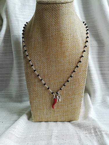 Collana girocollo stile rosario con filo di colore argento, cristalli neri e ciondoli con lettera e cornetto portafortuna rosso.