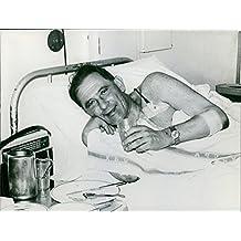 Vintage Foto de un hombre tumbado en una cama de hospital.