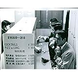 Vintage photo de chino hombres de pie en frente de un bar contador.