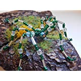 Perlenspinne in Grün und Silber auf Rinde