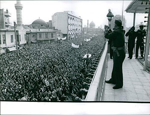 vintage-photo-of-abd-al-karim-qasim-stands-on-a-balcony-with-thousands-of-people-gathered-on-the-str