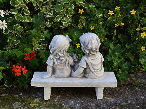 gartendekoparadies.de Wunderschöne Massive Kinderfigur auf der Bank aus Steinguss frostfest