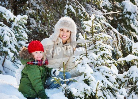 "Poster-Bild 40 x 30 cm: ""Winter outdoors can be fairytale-maker for children or even adults. Happy mother and child outdoors among snowy spruces"", Bild auf Poster"