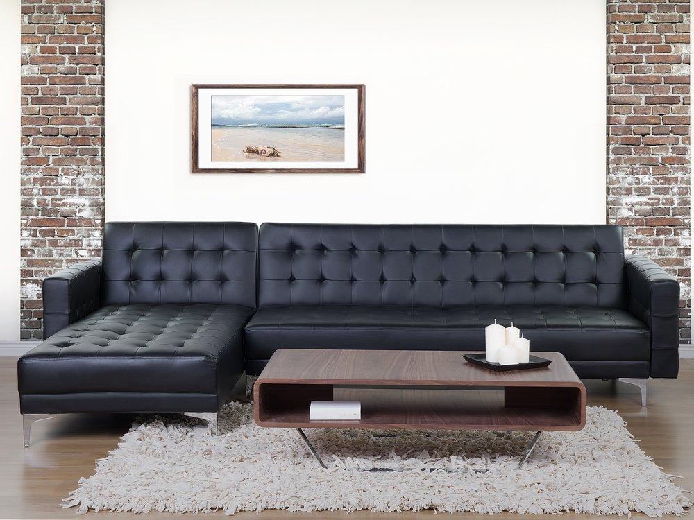 divano in pelle angolare di colore nero con bottoni, bel tavolino da salotto in legno scuro.