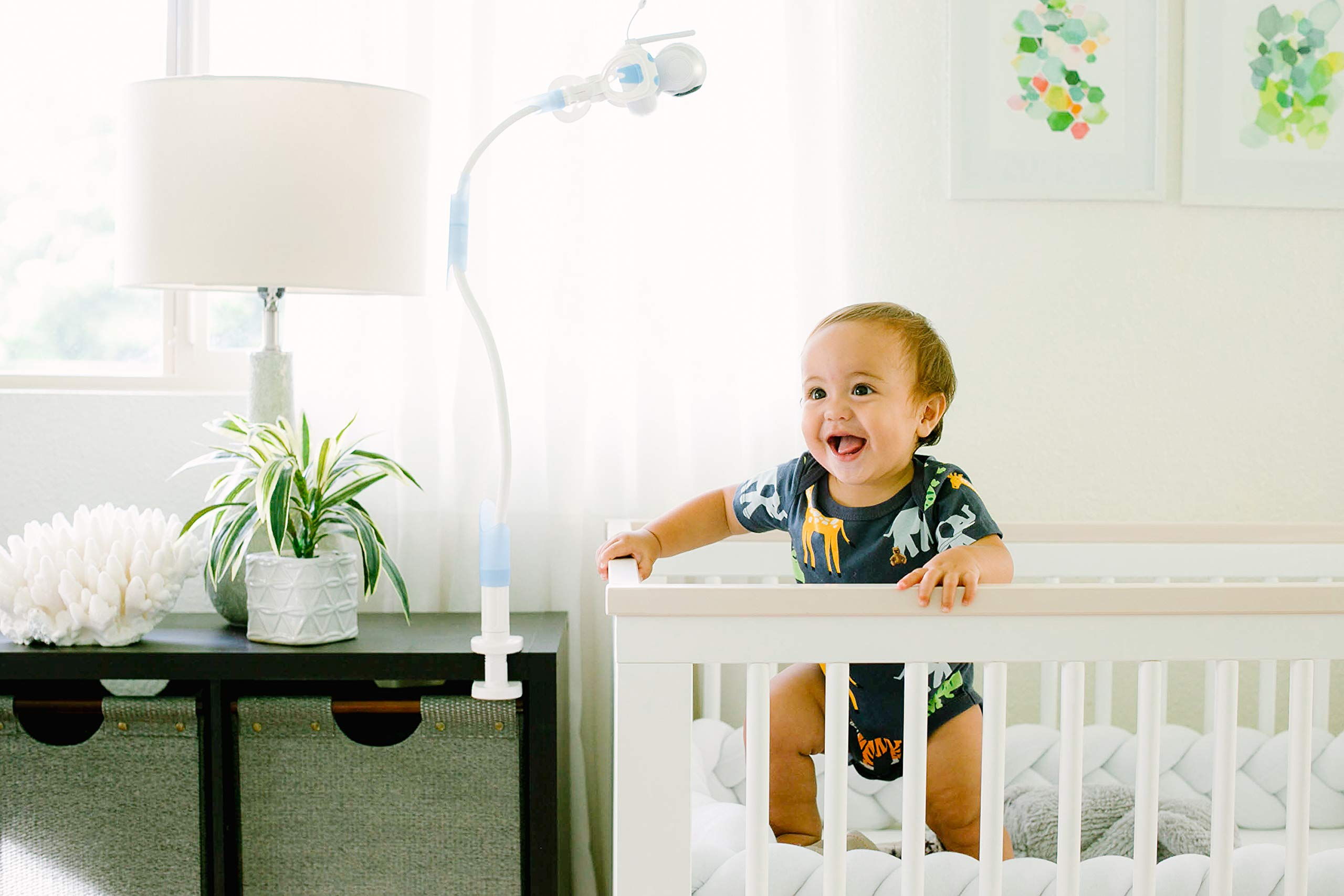 FlexxiCam   Universal Baby Camera Holder   Strong Flexible Baby Monitor Mount Shelf With Strap   No Drilling   A Safer Monitor Stand for Your Baby FlexxiCam GET THE BEST VIEW OF YOUR BABY - this flexible baby monitor holder allows you to get the perfect view of your infant. No more balancing of the baby camera on the edge of the cot. This baby camera shelf / holder can be attached to all kinds of furniture or a window sill to give you complete view of your sleeping baby. You can reposition and bend it to find the best spot from almost anywhere in the nursery. Your baby will never roll out of the view. No more coming back to readjust the monitor. UNIVERSAL FIT FOR MOST BABY MONITORS ON THE MARKET - this baby camera holder fits most baby video cameras with a base / stand less than 3.8 inches wide and 1.5 inches tall. We've tested the shelf with several leading baby monitor brands on the market (see our photos for examples of compatible camera types). Do not use FlexxiCam with a baby monitor that does not have a separate base / stand. If unsure, ask us if your baby monitor will fit. And if not, we'll always take it back! EASY TO USE, NO STICKING ON WALLS, NO DRILLING - the baby camera shelf has a strong clamp that holds securely to most surfaces, and is easy to attach on furniture in the room. Bend and rotate it to change the baby monitor position as required for best results. This camera holder is secure and strong. The baby video camera is firmly affixed within the clamp and supported by a rubber silicone strip. The holder does not damage the cot or furniture. PLEASE FOLLOW THE INSTALLATION INSTRUCTIONS. 4