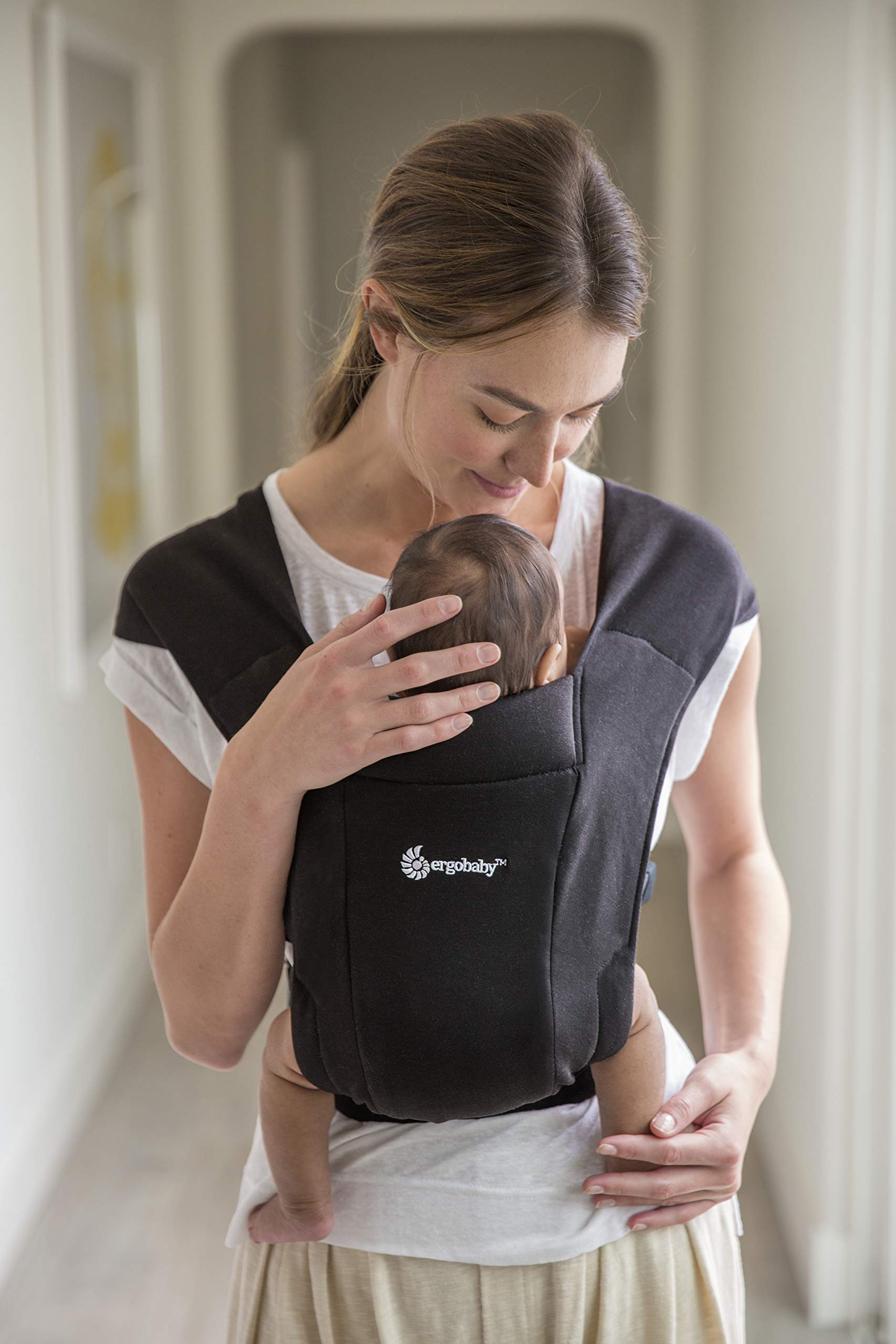 """ErgobabyEmbraceBaby Carrier for Newborns from Birth with Head Support, Extra Soft and Ergonomic (Pure Black) Ergobaby ERGONOMIC BABY CARRIER FROM BIRTH - Carry your newborn baby (3.2 - 11.3kg) snuggled close to you. The baby carrier supports the ergonomic frog-leg position (""""M"""" shape position) of the baby. NEW - The Ergobaby Embrace 2-position Carrier has been specially developed for newborns and babies. A baby carry system for quick and easy use. ULTRA-LIGHT & SUPER SOFT - Less material against the child and open-sided to allow good air circulation. Made from super soft jersey fabric, Oeko-Tex100 certified. Lightweight carrier (approx. 480g). 4"""