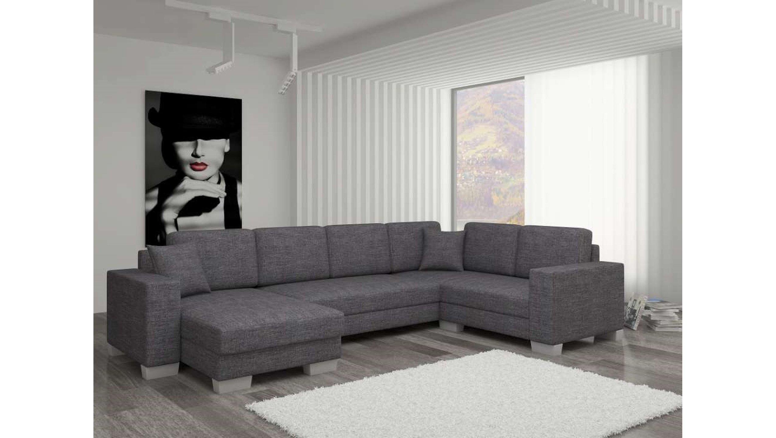 divano ad angolo con penisola in tessuto grigio scuro e tappeto bianco.