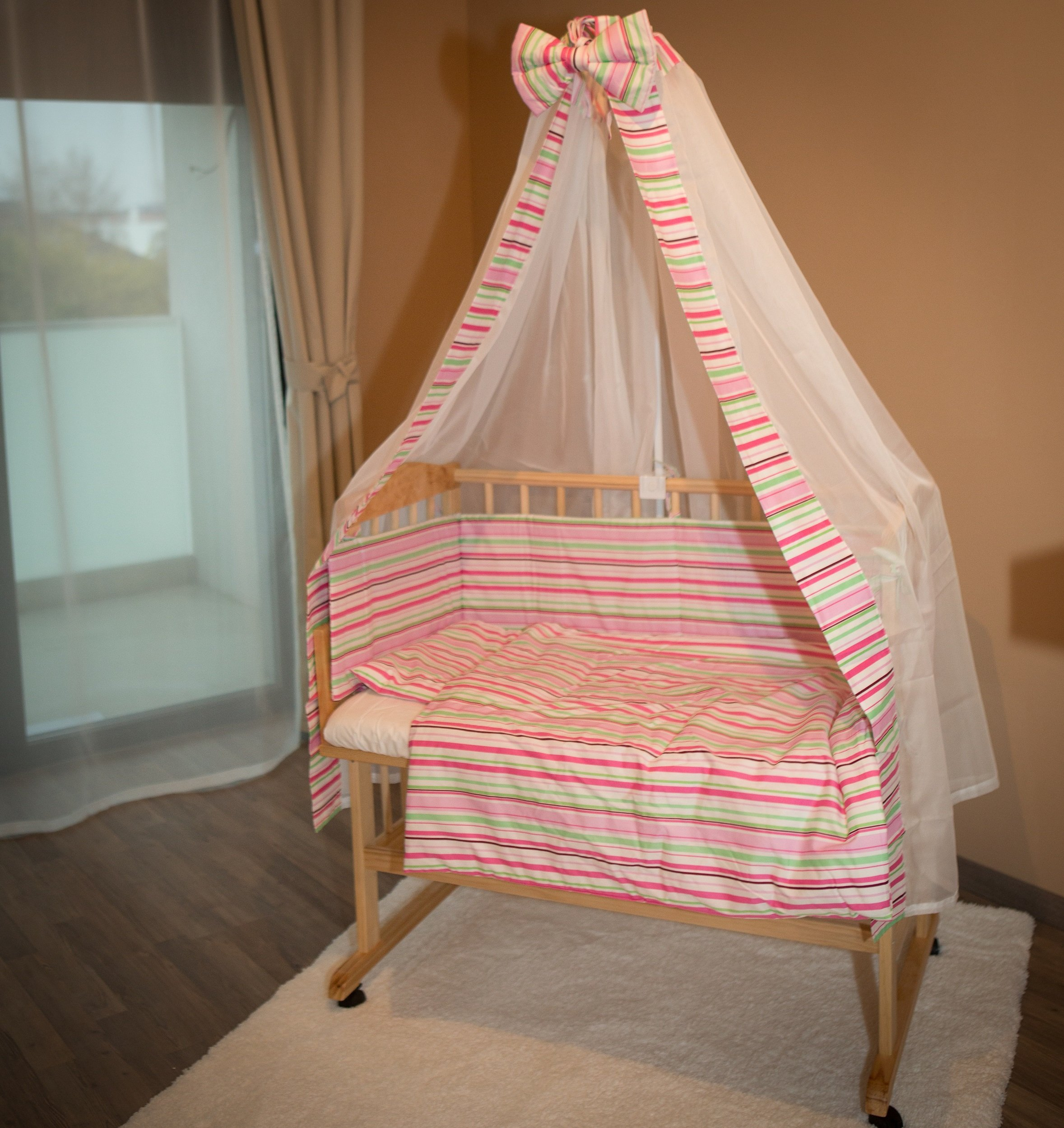 Bed side cot all inclusive 90x40cm, pink stripes Bambino World Main features:3 possible uses:Bed side cot (3 sides closed),Cot bed (4 sides closed),Child sofa;High quality pinewood;Height-adjustable duckboards;Inclusive bedlinen set, canopy and mattress; Bed side cot with large lying space 90 x 40 or 90 x 55cm (if you use the included additional board);Made of high-quality pinewood, clear-varnished with saliva-resistant toy´s paint with a high proportion of wax;Inclusive additional lateral part for use as a cot bed;Height-adjustable duckboards from 17 to 46cm to fit to the height of the parent´s bed; 4 movable castors, 2 with a brake;Overall dimensions 93 x 44/56 x 81cm; Accessories included in our offer:Mattress:High quality mattresses: soft foam polyurethane,Dimensions: 90 x (40+15)cm,Mattress cover: 100% cotton,Quilted on one side with washable fabric,Removable, machine washable at 60°C, 1