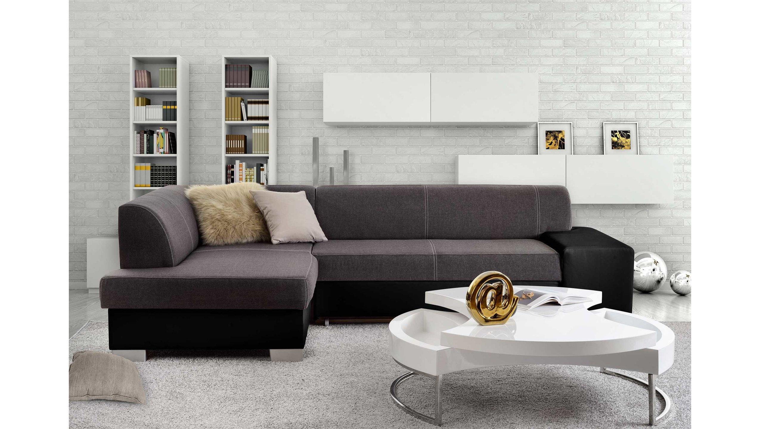 Divani ad angolo in tessuto grigio talpa e nero, tappeto grigio chiaro e tavolino bianco design.